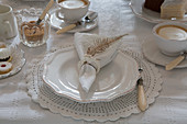 Table set in vintage style with white cloth, crockery and lace place mats