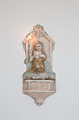 Antique sconce with angel and lit candle on wall