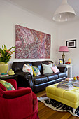 Black leather sofa below painting in colourful living room