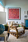 Rattan armchair in front of artwork and lamp on side table in living room