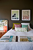 Scatter cushions and fabric samples on bed below pictures on dark wall in bedroom