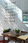 Wooden table and chairs and wall decoration made from wire springs