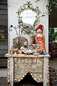 Exotic ornaments on small table covered in seashells