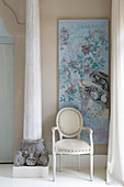 White Baroque chair next to antique pillar and in front of pale blue artwork