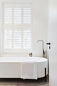 Moderne freistehende Badewanne unterm Fenster mit Fensterladen