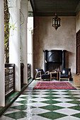 Armchairs in front of open fireplace in loggia with chequered floor