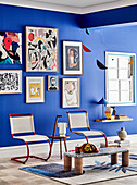 Cantilever chair, side table and low table in the room with works of art on a blue wall