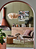 View through round arch on designer rattan table, chair, sideboard and fireplace in the living room with olive green wall