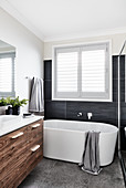 Free-standing bathtub below window and washstand with wooden doors in bathroom