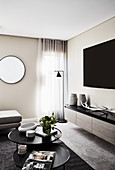 TV above low sideboard and set of coffee tables in elegant living room with round mirror on wall