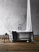 Freestanding bathtub with canopy and stool against gray wall