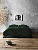Double bed with green bedspread and floor lamp against gray wall
