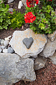 Heart-shaped pebble on stone garden wall