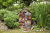 Handmade wooden insect hotel in natural-style garden