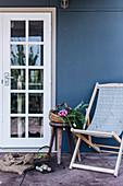 Liegestuhl und Körbe mit Ernte vorm Haus mit blauer Fassade