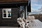 Rustic wooden chairs on veranda of cottage with view over imposing landscape