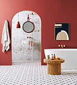 Freestanding bathtub and rattan table in the bathroom with brick-red wall and marble tiles, view of the sink through the arched opening