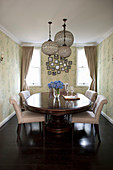 Antique, oval dining table with pale upholstered chairs and pendant lamps in dining room with patterned wallpaper