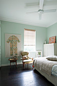 Bed, white cupboard, easy chair next to window and child's clothing decorating wall in pastel-green room