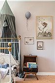 Metal bed with grey canopy and wall painted pink in nurserey