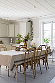 Bistro chairs around dining table with tablecloth in rustic kitchen-dining room