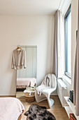 Free-standing mirror and classic chair next to window in bedroom