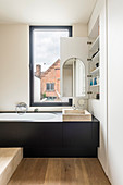 Bathtub with black surround below window and fitted cupboard with mirror inside open door