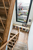 Stairwell with wooden stairs, bookcase and window