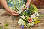 Sommerlicher Blumenstrauß wird gebunden