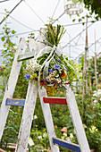 Sommerlicher Blumenstrauß hängt an einer Leiter im Gewächshaus