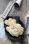 Gluten-free, heart-shaped lavender biscuits next to paper cone and test tube filled with lavender flowers