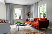 Red sofa in living room with pale grey curtains