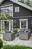 Pale grey seating on terrace outside wooden house