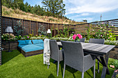 Garden table and loungers in garden with raised beds and screen fences