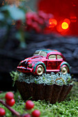 Winter arrangement of barbed-wire plant and toy car in vintage cake tin