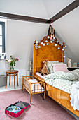 Antique wooden bed and dolls' bed in girl's bedroom