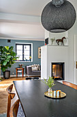View across dining table to fireplace, houseplant, side table and sofa