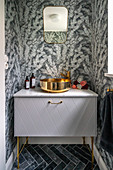 Washstand with modern sink in bathroom with grey patterned wallpaper
