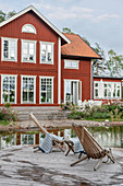 Loungers on jetty next to pond outside Falu-red Swedish house