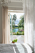 View from bedroom into summery garden with lake
