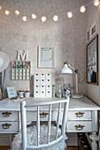 Spoke-back chair at vintage-style desk below fairy lights