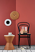 Handcrafted, Viennese cane wall clock on red-painted wall, chair, ornaments and side table