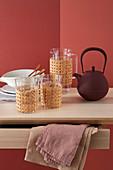 Gläser und Kanne umhüllt mit Wiener Geflecht, Teekanne und Teller auf Tisch