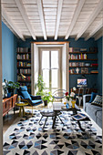 Rug with geometric pattern in living room with blue walls and retro furnishings