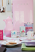 Table set in feminine style with pink coffee pot and kitschy accessories