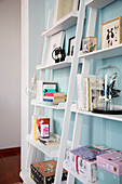 Books and knick-knacks on white angled shelves against pale blue wall