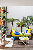Metal bed used as sofa on summery terrace decorated with palms and cacti