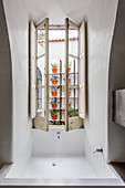 Fitted bathtub below casement window in Mediterranean bathroom
