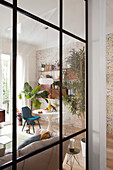Blick durch raumhohe Glastrennwand in Wohnbereich mit Esstisch