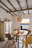 Designerstühle am Esstisch mit Blick aufs Meer bei Abendstimmung